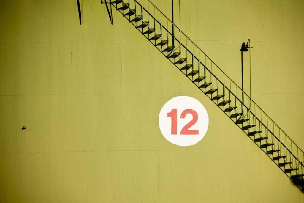 Nell'immagine una scala con un murales sul muro che raffigura il numero 12